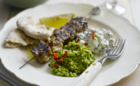 Grilled lamb skewers with crushed peas, tzatziki and chilli